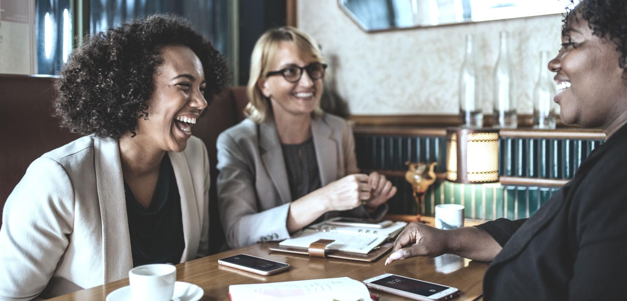 Parceria Core - Mulheres felizes na mesa discutindo negócios